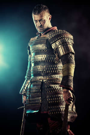 Portrait of a courageous ancient warrior in armor with sword. photo
