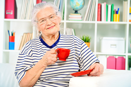 Smiling senior woman sitting at home on a sofa and drinking tea. photo