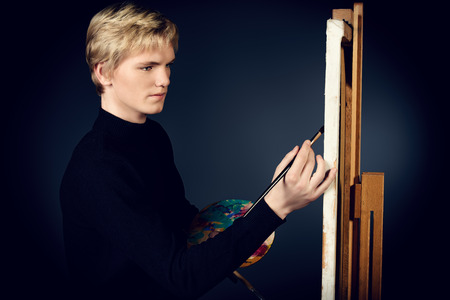 Young man artist paints on canvas with oil paints. Studio shot over black . photo