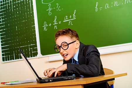 Funny schoolboy in a suit working on a laptop at school. Education. photo
