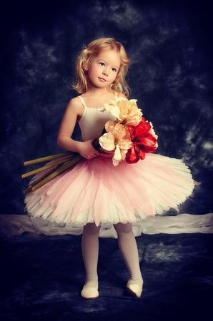 Pretty little girl ballerina in tutu posing over vintage . photo
