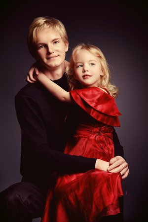 Portrait of an elder brother and his little sister over black . photo