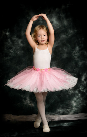 Pretty little girl ballerina in tutu posing over vintage .