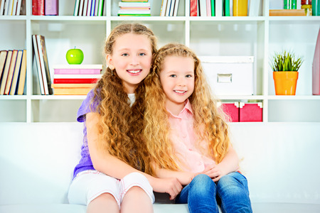play room: Two beautiful joyful sisters sitting on a sofa at home.