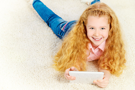 Cheerful little girl lying on a carpet at home and playing with a digital tablet. photo
