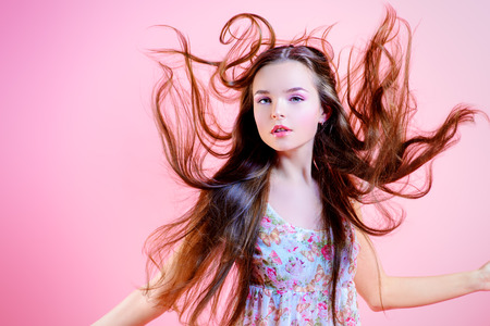 cabello largo y hermoso: Muchacha elegante con el maquillaje natural y el pelo largo y hermoso en la presentaci�n de movimiento sobre fondo rosa. Moda. Pelos.