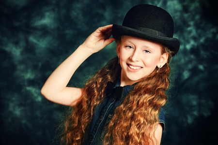 Portrait of an elegant teen girl wearing retro dress and bowler hat. photo