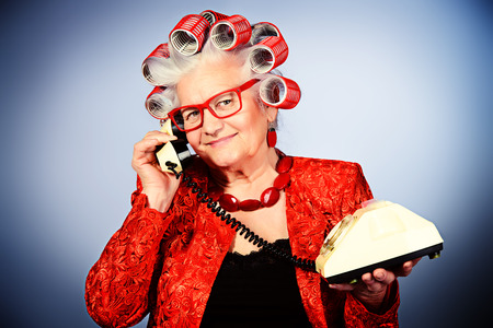 Portrait of an elderly woman in curlers talking on the phone. photo