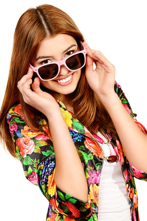 Portrait of a beautiful cheerful woman in summer clothes and sunglasses smiling at the camera. Isolated over white.