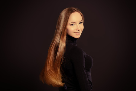 magnificent: Beautiful girl with magnificent long hair posing over black background.
