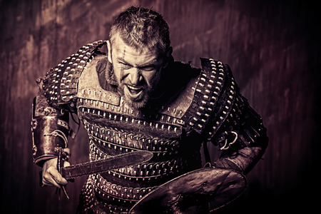 courageous: Portrait of a courageous ancient warrior in armor with sword and shield.