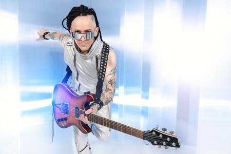 modern rock: Modern rock musician posing with his electric guitar. Futuristic style. Stock Photo