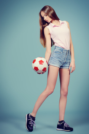 Beautiful girl teenager wearing sportive clothes posing at studio with a ball. Full length.  photo