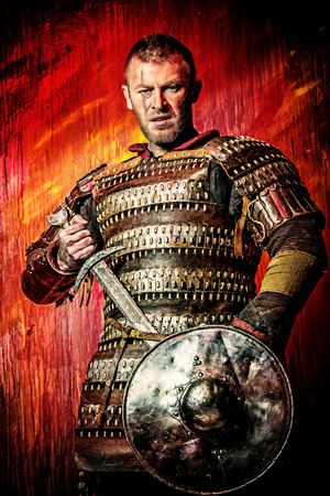 Portrait of a courageous ancient warrior in armor with sword and shield. photo