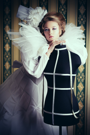 Beautiful fashion model in the refined white dress and elegant hat. Vintage style. Art project. Haute Couture. photo