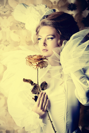 Beautiful fashion model in the refined white dress and elegant hat. Vintage style. Art project. photo