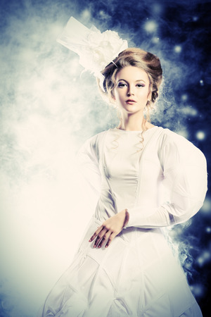 'retro styled': Portrait of a beautiful fashion model in the refined white dress and elegant hat. Snow queen. Winter fantasy. Stock Photo