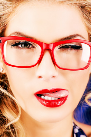 Close-up portrait of a charming pin-up woman with red lips and reg glasses. photo