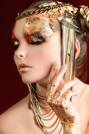 Art project: beautiful woman with golden make-up. Jewelry, make-up. Fashion. photo