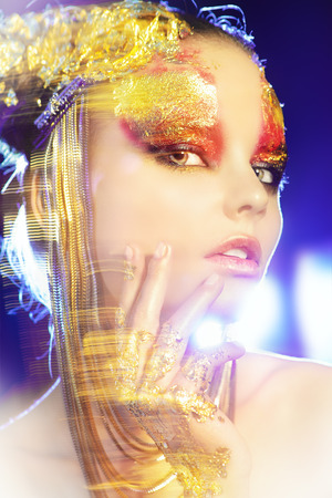 Art project: beautiful woman with golden make-up. Jewelry, make-up. Fashion. Light effects. photo