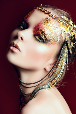 Art project: beautiful woman with golden make-up.  photo
