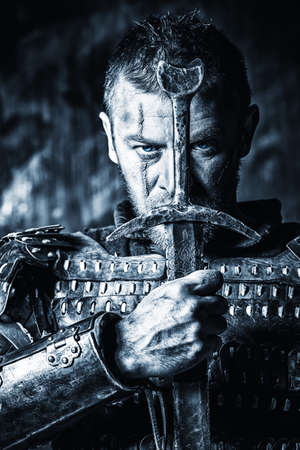 ancient warrior: Portrait of a courageous ancient warrior in armor with sword and shield. Black-and-white photo.