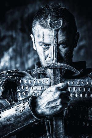 espadas medievales: Retrato de un antiguo guerrero valiente en armadura con la espada y el escudo. Blanco y negro foto. Foto de archivo