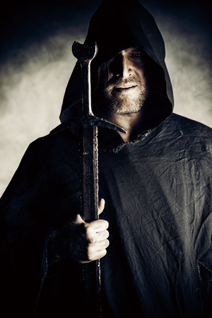 Portrait of a courageous warrior wanderer in a black cloak and sword in hand. Historical fantasy. photo