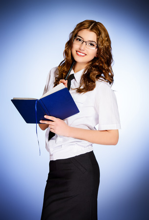 Portrait of a beautiful young businesswoman standing with diary. photo
