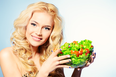 Portrait of a beautiful young woman eating vegetable salad. Healthy life. Diet. photo