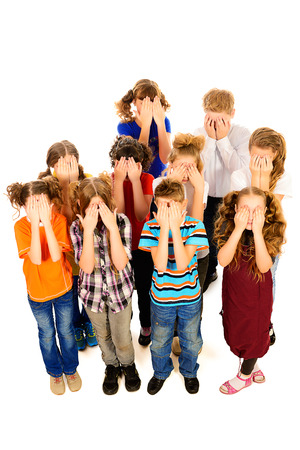 Children stand together and cover their faces with hands. Isolated over white. photo