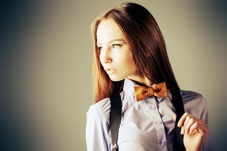Elegant girl model poses in blouse and bow tie. Fashion shot.  photo