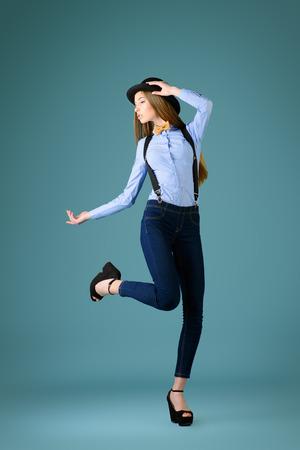 poses de modelos: Modelo elegante chica posa en la blusa, corbata de lazo y sombrero hongo. Estilo refinado de la vieja Europa.