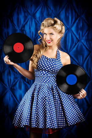 'retro styled': Pretty pin-up woman with retro hairstyle and make-up posing with vinyl record over vintage background. Stock Photo