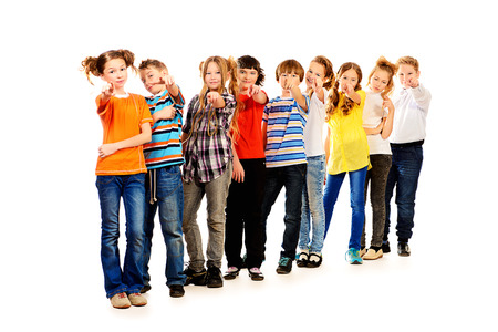 group direction: Group of children standing together and show a finger at the camera. Isolated over white.