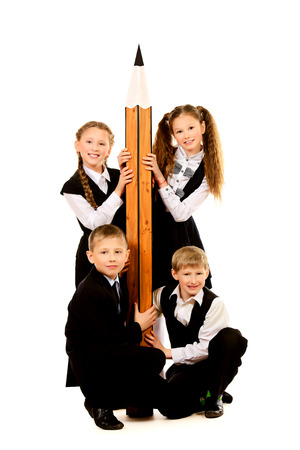 Cheerful schoolgirls and boys stand together and hold a huge pencil. Educational concept. Isolated over white.