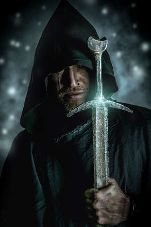 warrior sword: Portrait of a courageous warrior wanderer in a black cloak and sword in hand. Historical fantasy.
