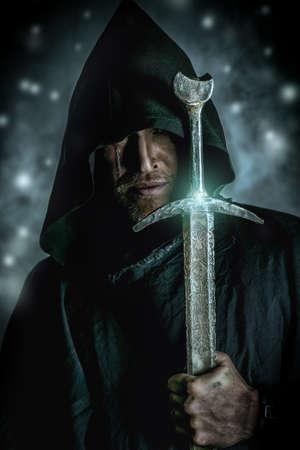 guerrero: Retrato de un guerrero valiente trotamundos en un manto negro y una espada en la mano. Fantas�a hist�rica. Foto de archivo