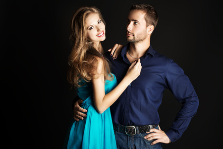 Portrait of a beautiful young couple in love posing at studio over dark background. photo