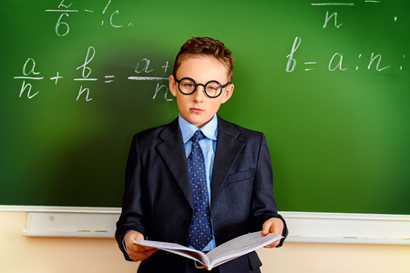 Smart schoolboy stands at the blackboard in the classroom with opened book. Education. photo