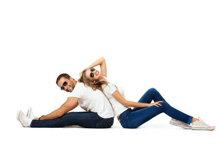 women jeans: Happy emotional young couple in love posing at studio. Isolated over white. Stock Photo