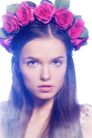 Fashion shot of a beautiful girl in a wreath of roses and light summer dress. Spring, summer romance. photo