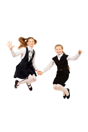 uniforme escolar: Two Ten años de muchachas en un salto uniforme de alegría. Aislado en blanco.