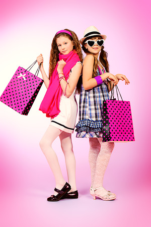 Two pretty fashion girls with shopping bags posing over pink background.