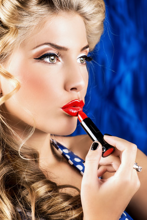 Portrait of a charming pin-up girl painting lips with red lipstick. Stock Photo - 27043753