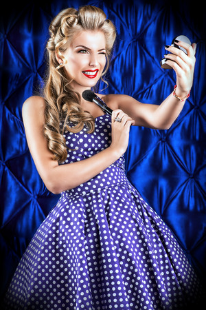 Portrait of a charming pin-up girl painting lips with red lipstick. Stock Photo - 27043693