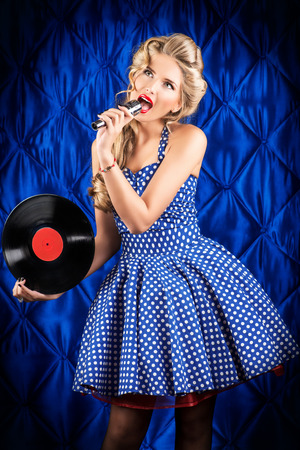 Pretty pin-up woman singing with vinyl record over vintage background. Stock Photo - 27043700