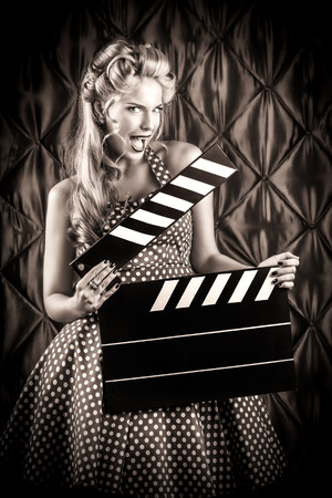 Pretty pin-up woman with retro hairstyle and make-up posing with clapper board over vintage background. Black-and-white photo. Stock Photo - 27043705