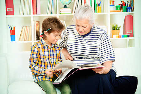 grannies: A grandmother sitting at home on a sofa with her grandson and reading a  book.