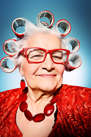 curlers: Portrait of an elderly woman in curlers looking at camera.